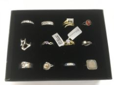 A collection of 12 silver rings, some new.