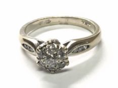 An 18carat gold ring set with a pattern of diamonds the shank set with further diamonds. Ring size
