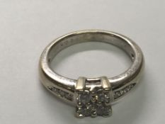 A 18 carat gold ring set with a pattern of diamonds with diamonds set in the shank ring size K.