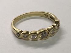 An 18carat yellow gold ring set with eight diamonds with a woven effect shank. Ring size L.