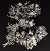 Two silver charm bracelets with over 40 silver charms including rabbit, train, caravan, boat, hat,