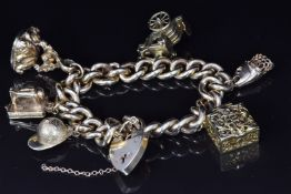 A 9ct gold charm bracelet with five 9ct gold charms including sewing machine, fob, jockey's hat