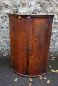 An oak and mahogany veneered bow front hanging corner cupboard, 104cm high x 68cm wide. This lot can