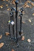 A wrought iron four piece fire companion set. This lot can only be collected on Saturday 19th