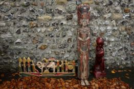A red stained tribal figure; together with another figure; and a carved figure group. This lot can