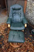 A modern green leather adjustable armchair; together with a matching footstool. This lot can only be
