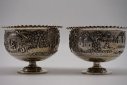 A pair of Indian white metal pedestal bowls, decorated village scenes, 8.5cm high.