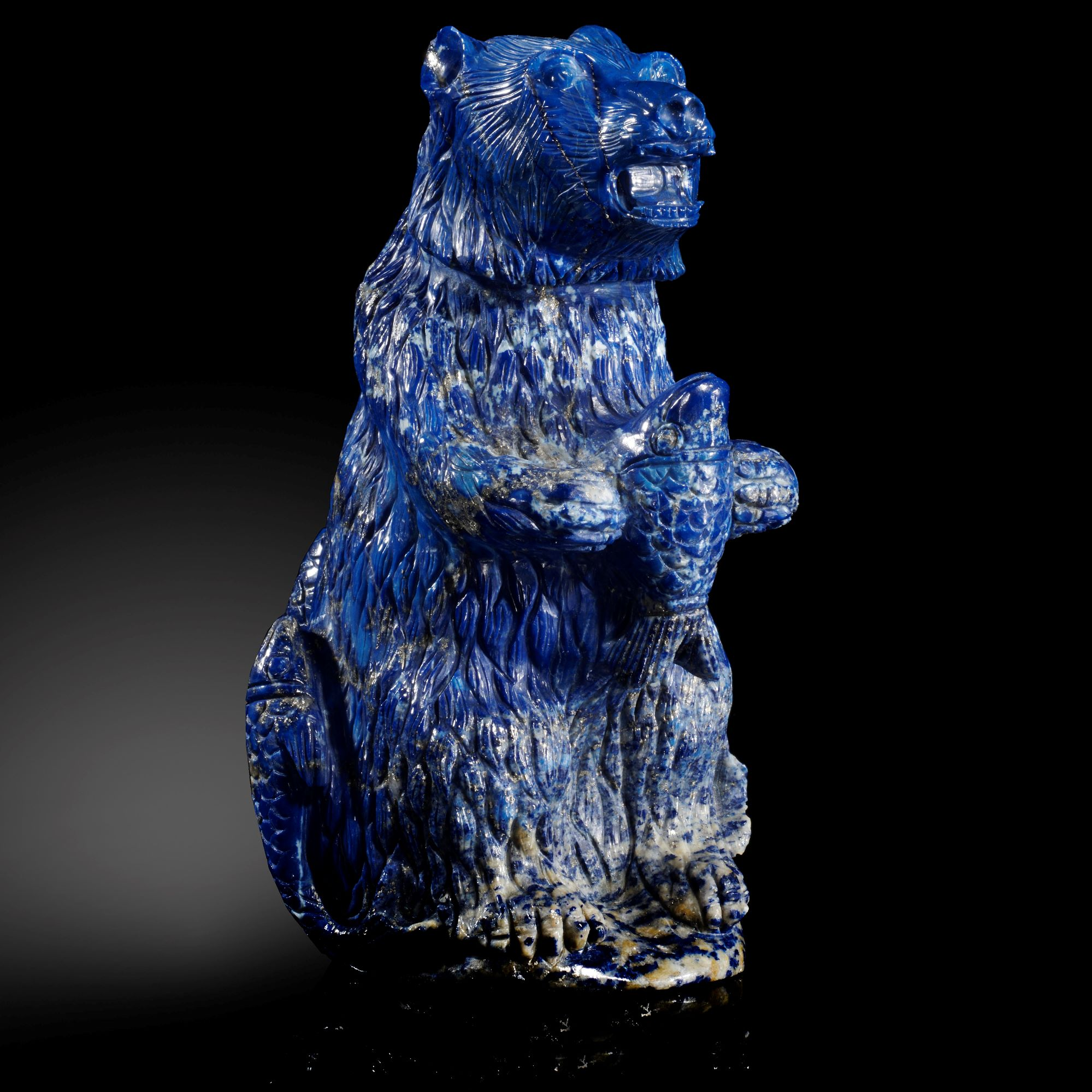 Lot 22 - Interior Design/Minerals: A carved Lapis lazuli bear holding a salmon, in fitted box, 17cm high