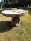 Garden Tables/Furniture: A carved stone table with millstone top on staddlestone base, 122cm