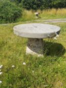 Garden Tables/Furniture: A carved stone table with millstone top on staddlestone base, 80cm high