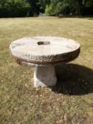 Garden Tables/Furniture: A carved stone table with millstone top on staddlestone base, 107cm