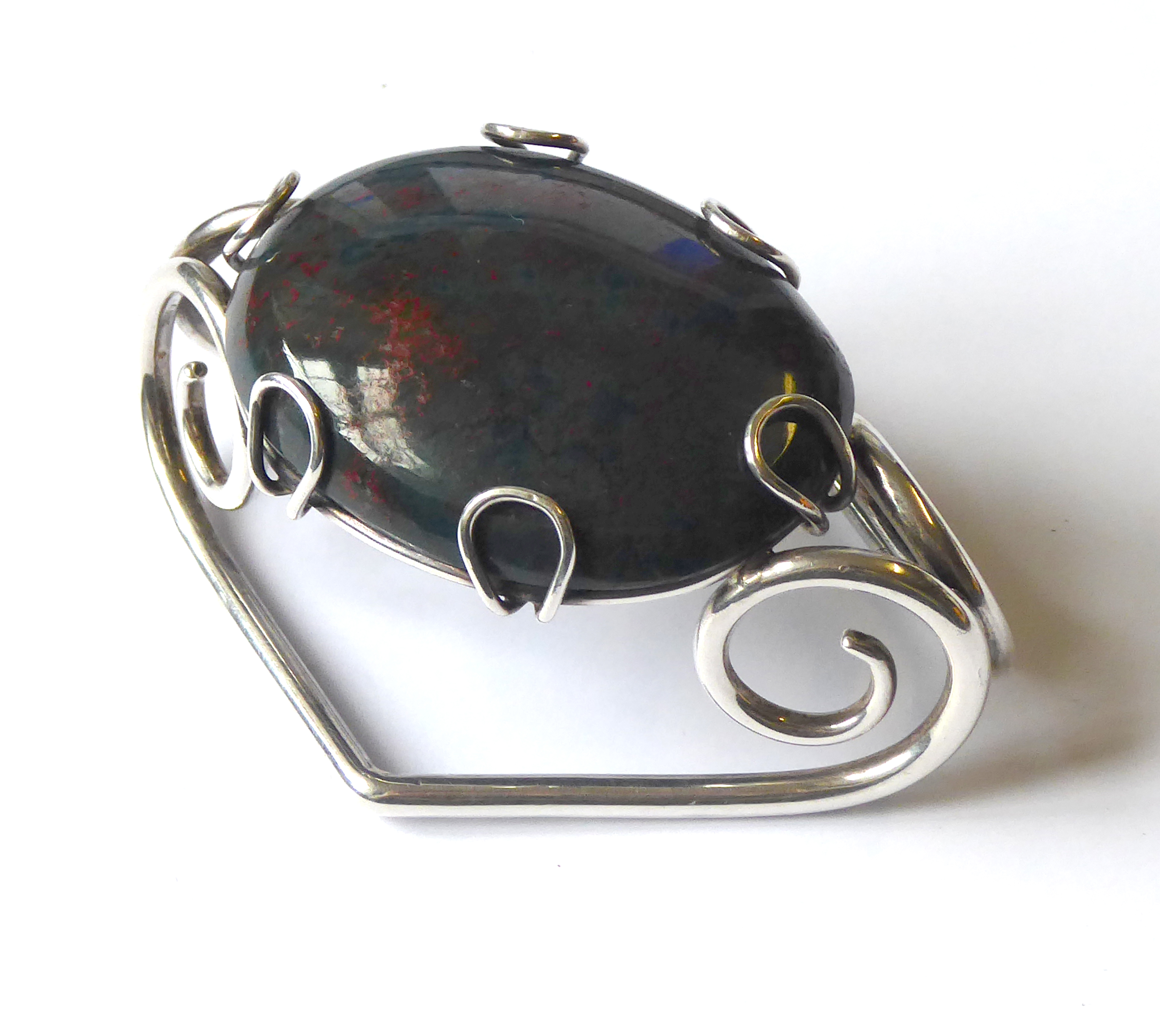 Lot 2 - AN EARLY 20th CENTURY CASED WHITE METAL AND BLOODSTONE SCARF CLIP An oval cabochon cut stone in a