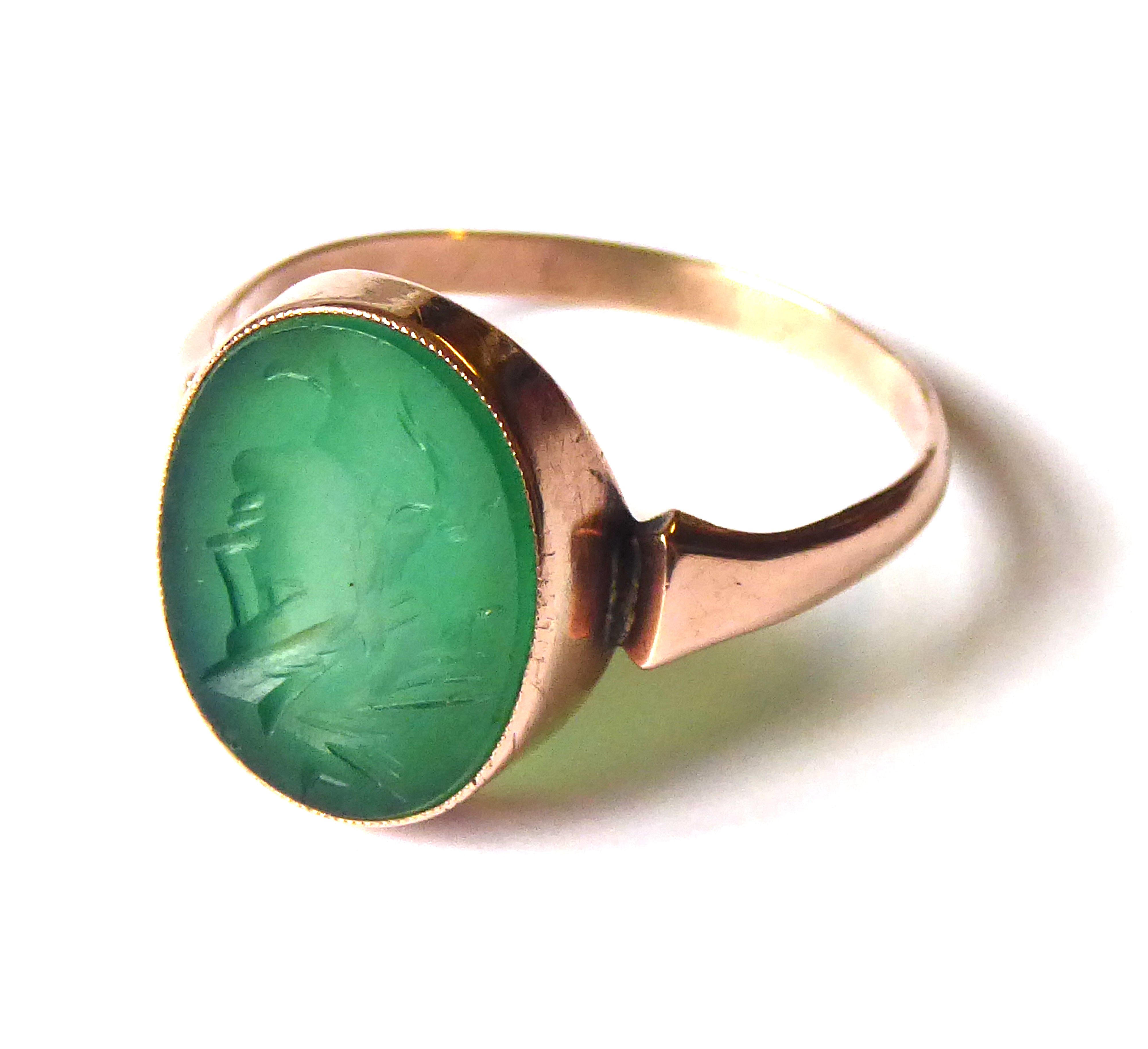 Lot 6 - A LATE 19th/EARLY 20TH CENTURY YELLOW METAL AND HARD STONE INTAGLIO SIGNET RING Having an oval green