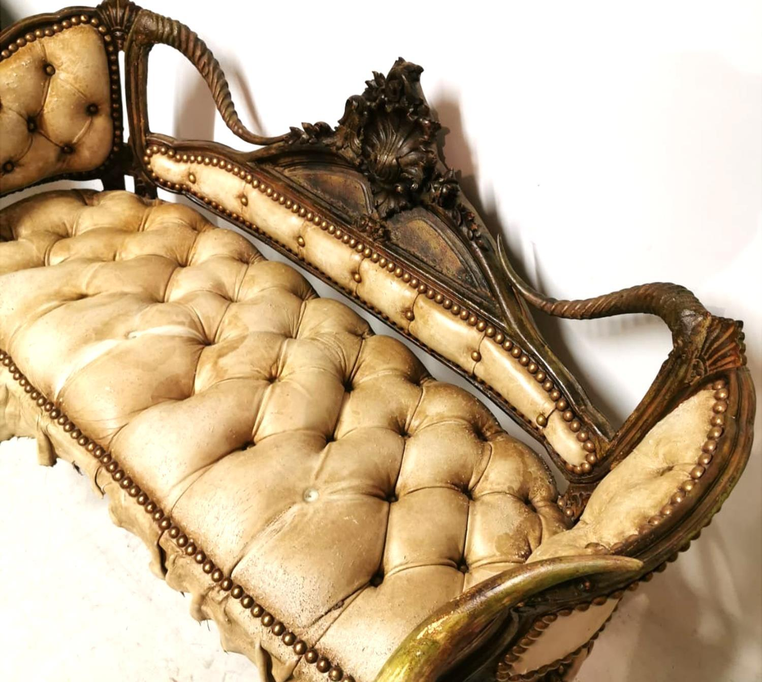 Lot 717 - A CONTINENTAL TWO SEAT SETTEE With carved central cartouche flanked by horns, upholstered in a cream