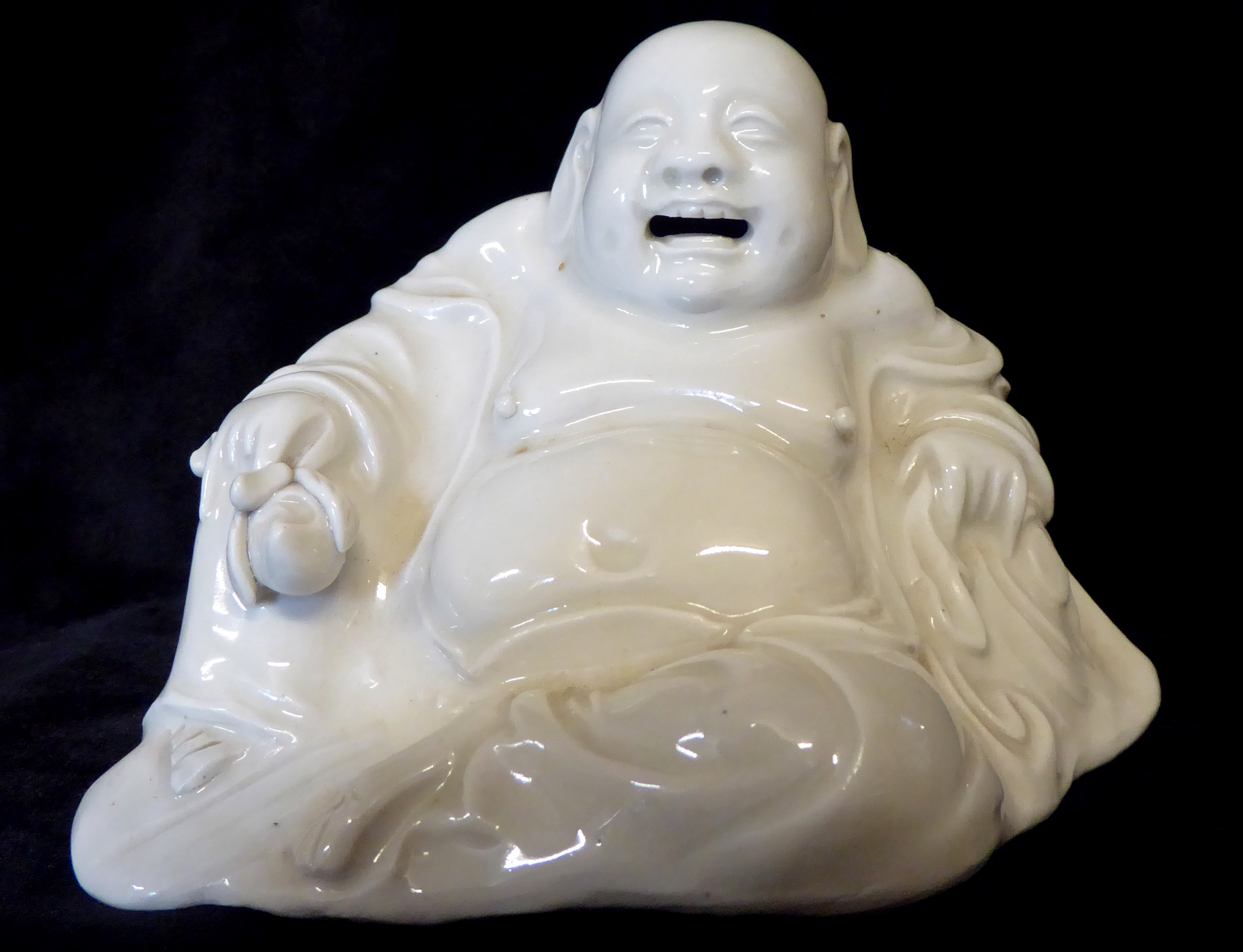 Lot 154 - A CHINESE BLANC DE CHINE PORCELAIN BUDDHA In seated pose holding a peach Inscribed in pencil to base