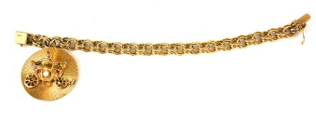 A 14CT GOLD BRACELET HUNG WITH A 14CT GOLD, RUBY AND PEARL ENCRUSTED ROYAL COACH ROUNDEL. (20cm,