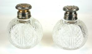 A PAIR OF VICTORIAN SILVER AND CUT GLASS PERFUME BOTTLES Having chased screw caps with internal