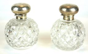 A PAIR OF EDWARDIAN SILVER AND HOBNAIL CUT GLASS PERFUME BOTTLES Spherical hinged lids, hallmarked