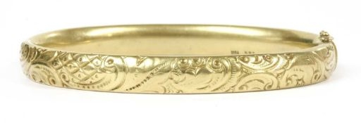 A gold hollow hinged oval bangle,