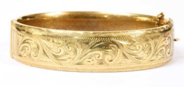A 9ct gold oval hinged bangle,