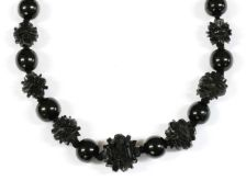 A single row graduated carved jet bead necklace,