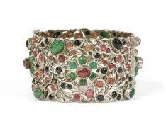 A silver hinged emerald, ruby and sapphire set bangle,