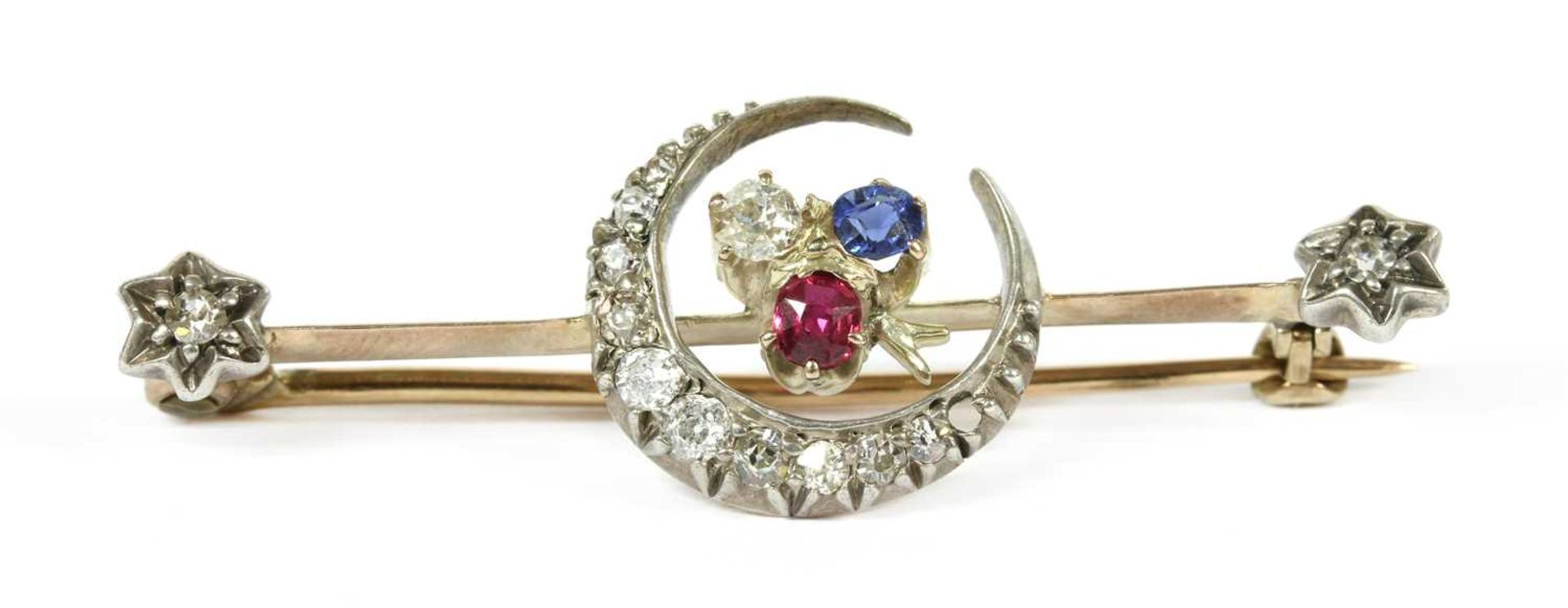 A gold and silver, diamond, ruby and sapphire crescent bar brooch,