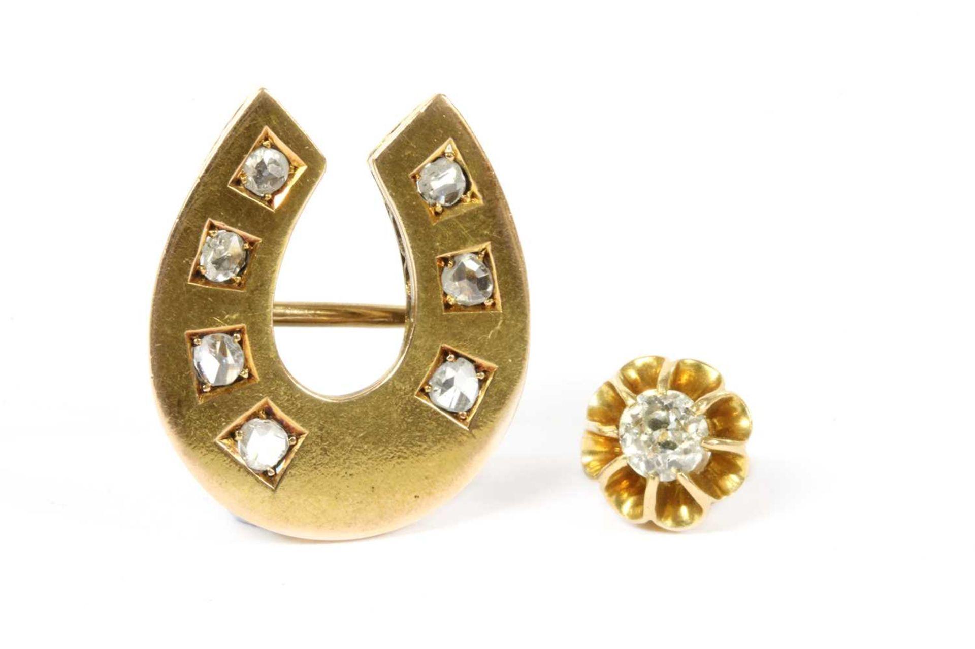 A gold diamond horseshoe brooch,