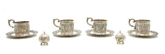 A set of four Indian silver cup holders and saucers,
