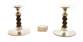 A pair of turned wooden on white metal mounted candlesticks,