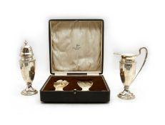A cased silver sugar caster and cream jug set,