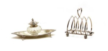 An oval silver ink stand with cut glass well,