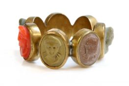 A late Georgian gilt metal specimen lava and coral cameo ring,