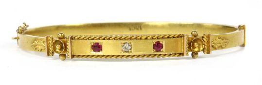 A gold diamond and ruby set oval hinged bangle,