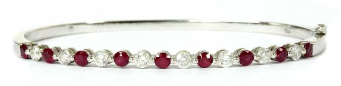 A white gold ruby and diamond hinged bangle,