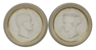A pair of carved marble roundels,