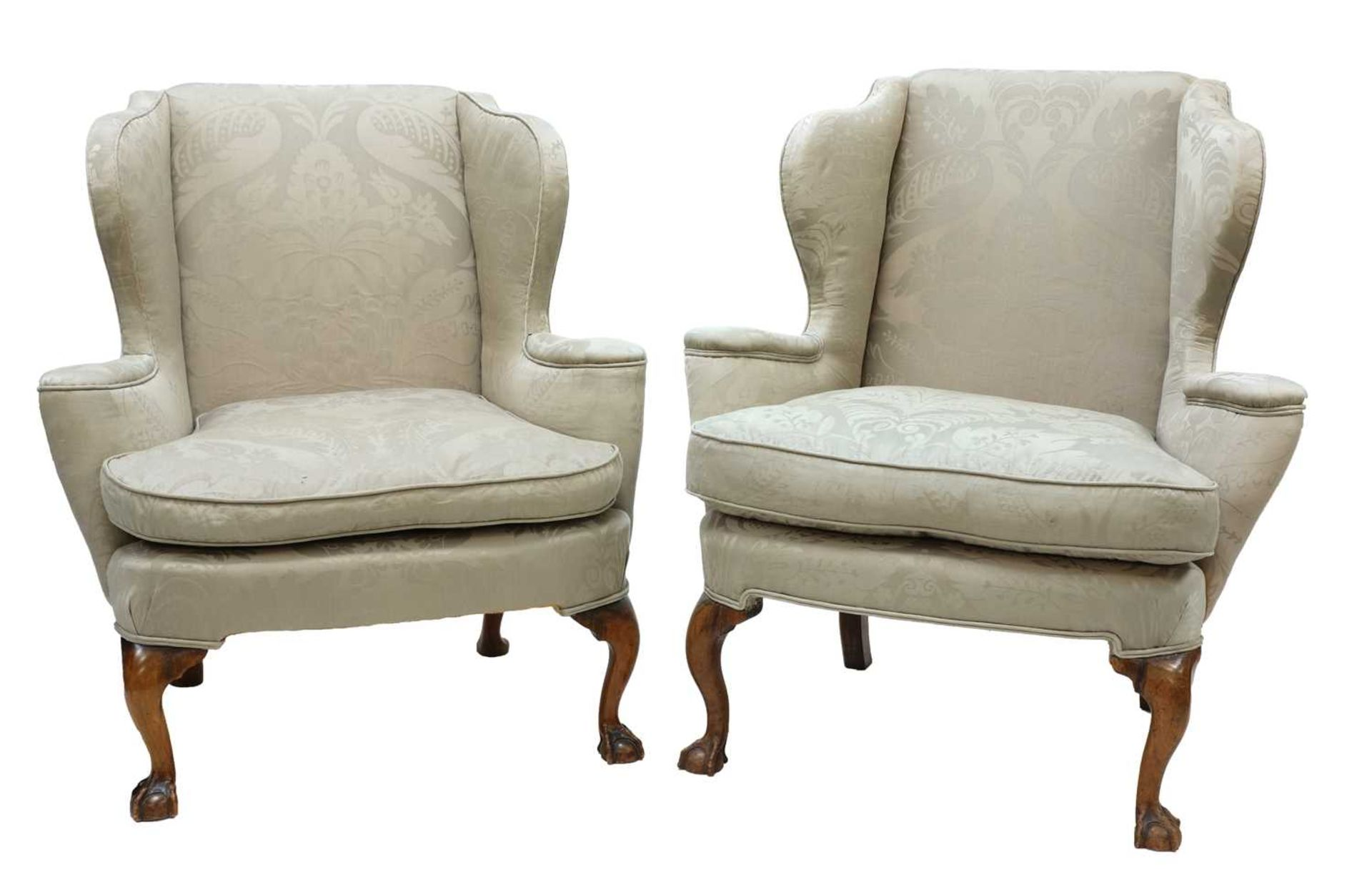 A closely matched pair of George III-style wing back armchairs,
