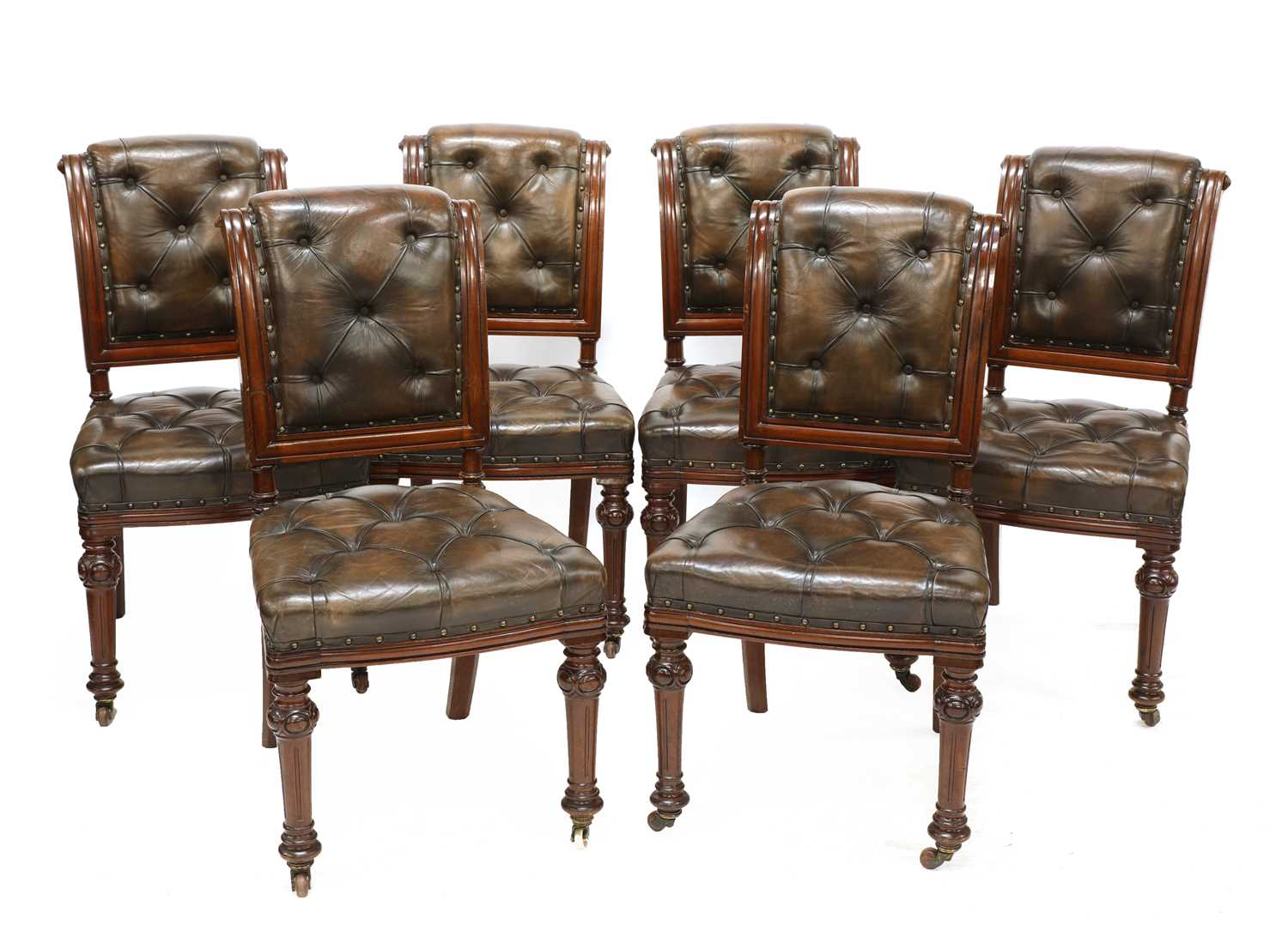 A set of six Victorian walnut and buttoned leather upholstered dining chairs,
