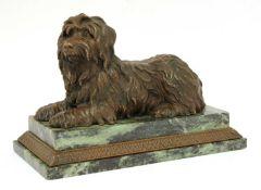 A bronze figure of a recumbent terrier,