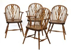 A set of four walnut and fruitwood wheel back Windsor chairs,