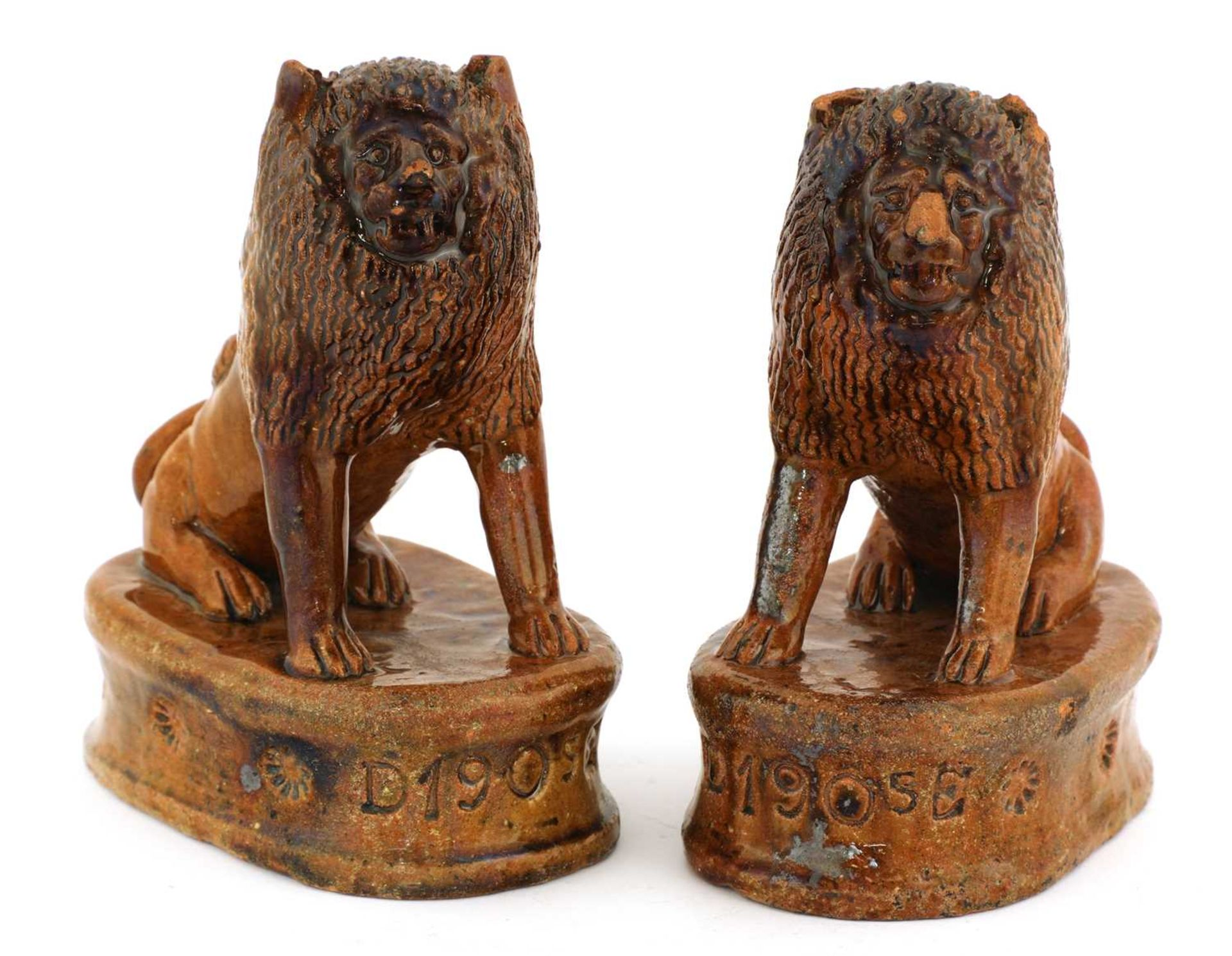 A pair of treacle-glazed pottery lions,