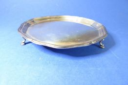 A small hallmarked silver salver with pie-crust edge and raised on three cast feet; Sheffield