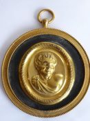 A 19th century circular gilt-metal wall-hanging relief study of a young male figure with curly