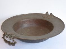 A large late 19th/early 20th century circular two-handled Eastern copper bowl; heavy, ornately