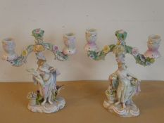 An interesting pair of 19th century hand-decorated continental porcelain two-light candelabra;