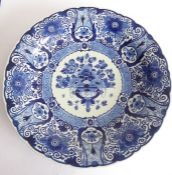 A large early 20th century Dutch Delft charger; the border decorated with flower heads and