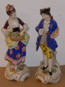 A pair of late 19th century hand-decorated continental porcelain figures; the lady with hair tied up