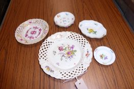A porcelain group of mostly Meissen; a reticulated dish hand-decorated with a floral spray, one