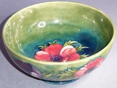 A William Moorcroft pottery bowl in theAnemone pattern; central tube-lined flower with similar