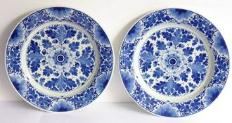 A pair of early 20th century Dutch Delft ware chargers; each centrally decorated with a flower